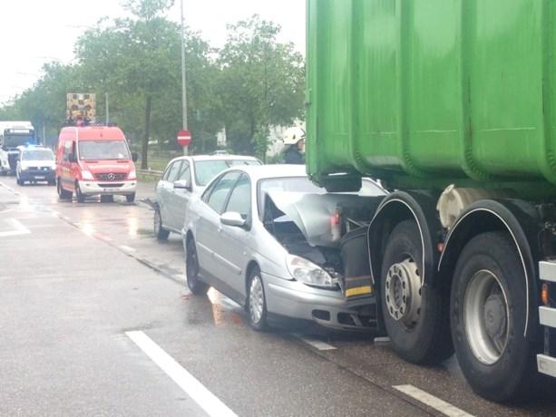 Auto belandt onder vuilniswagen
