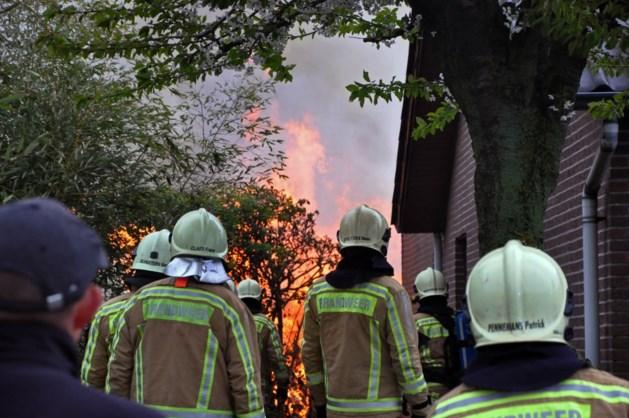 Houtopslag brandt uit achter woning