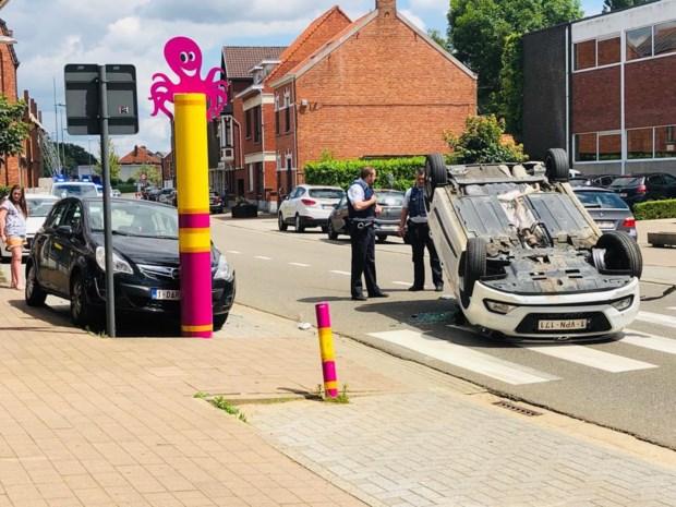 Auto belandt op zijn dak aan schoolpoort