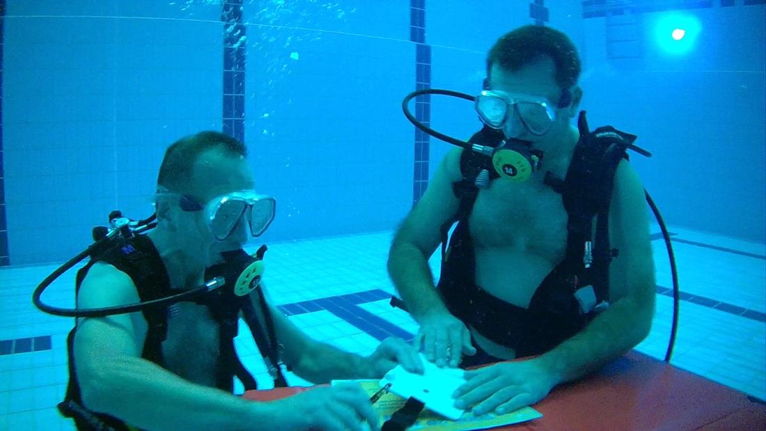 Bilzense schepen en functionaris duiken naar bodem van zwembad om overeenkomst te tekenen