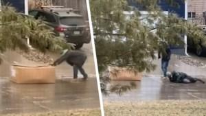 Pakjesbezorgers verkeren minutenlang in moeilijkheden door spekgladde helling, tot hilariteit van buurtbewoner