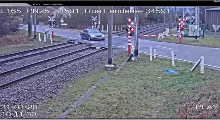 Chauffeur die rood stoplicht negeert, ontsnapt nipt aan aanstormende trein
