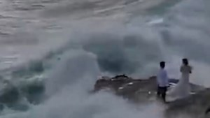 Pasgetrouwd koppel maakt foto's op het strand, maar grote golf brengt daar abrupt einde aan