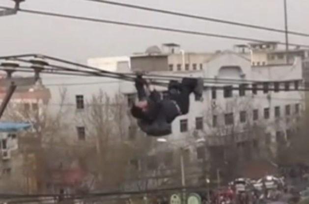 Dronken Chinees bengelt aan elektriciteitskabel (video)